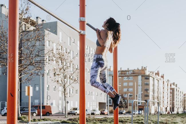 Woman training on parallel bars on street