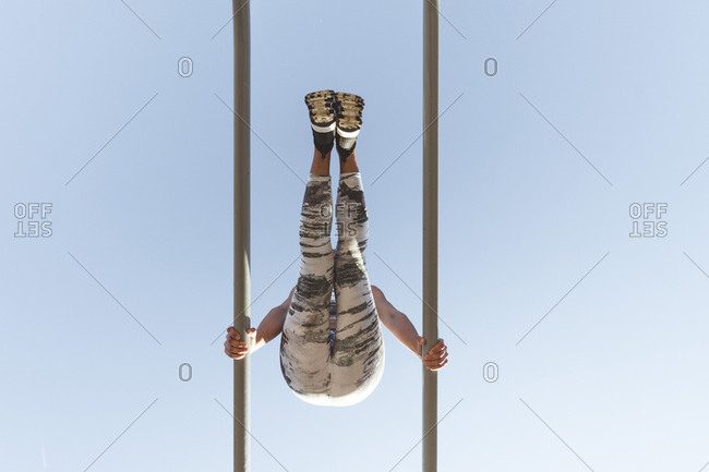From below lady in sportswear doing exercises on parallel bars and blue sky