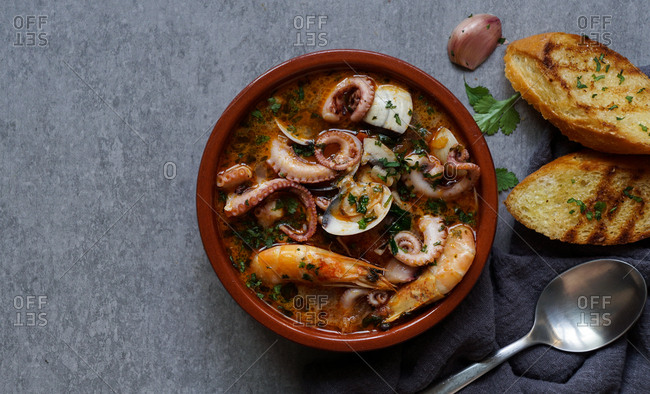 From above bowl of soup with shrimps, octopus and herbs near spoon, garlic and slices of bread on grey background