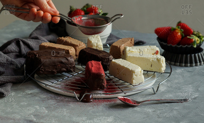 Crop hand of human pouring red sugar powder on tasty fresh strawberry and chocolate cheese curds on tray