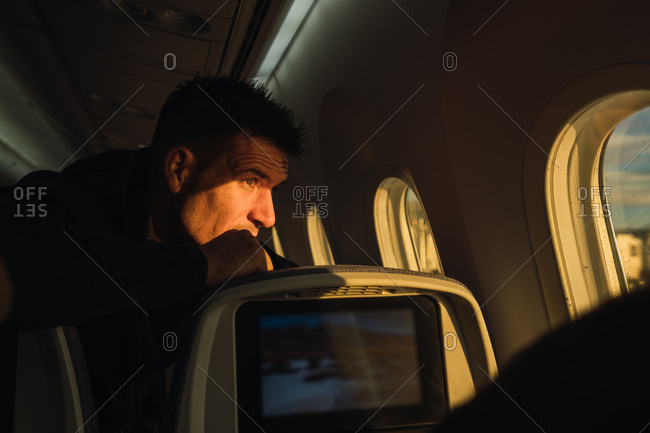 Side view of adult male looking out window of modern aircraft and thinking during flight