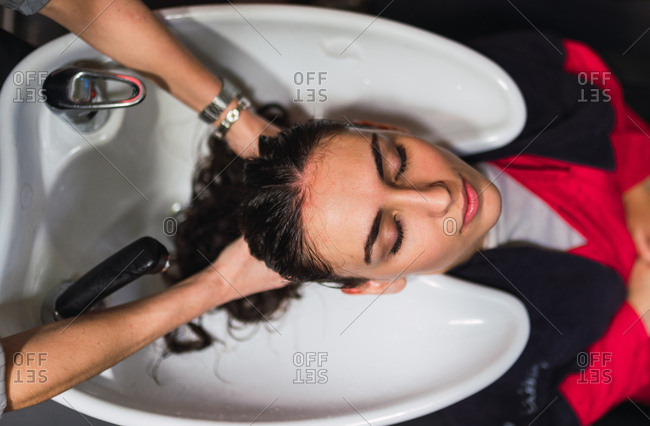 From above woman washing hairs to attractive lady with closed eyes in sink