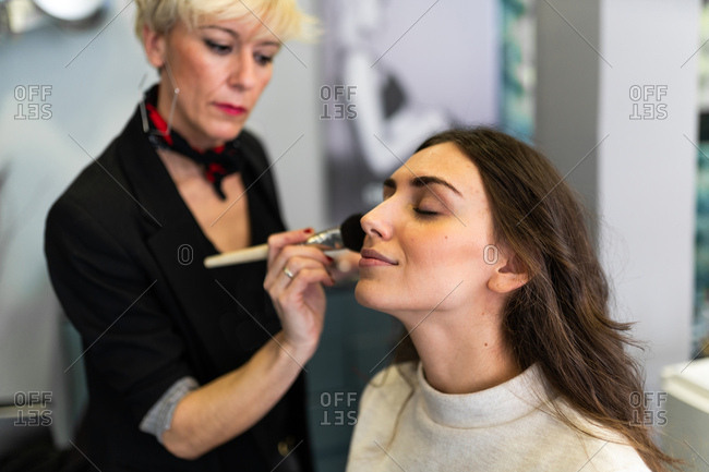 Stylist rouging lips by brush to attractive woman with makeup on blurred background