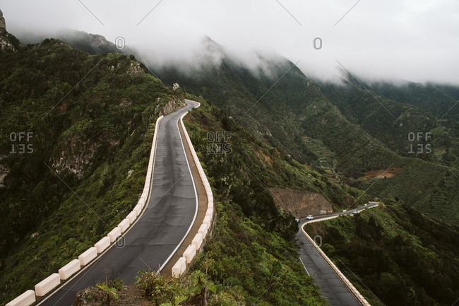Two asphalt roads going through mountain ridge on wonderful misty day in majestic countryside