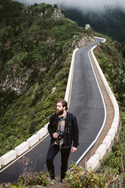 Bearded photographer looking away on mountain road