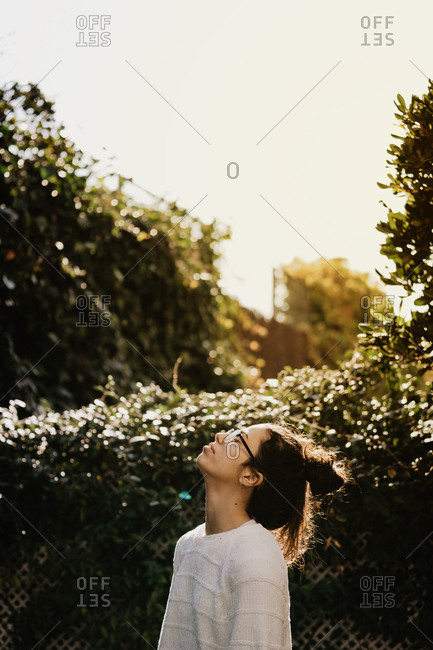 Side view of pretty young female stylish sweater and glasses looking up while standing near bushes in garden