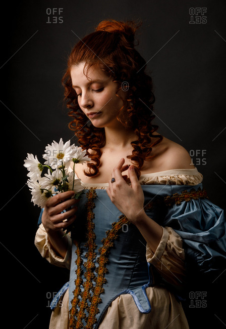 Baroque woman with closed eyes holding flowers