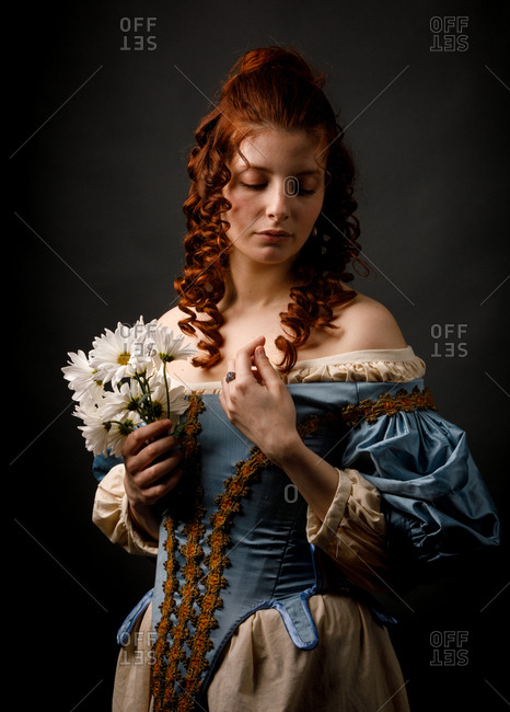 Pretty woman in medieval dress keeping eyes closed and holding bunch of white flowers while standing on black background
