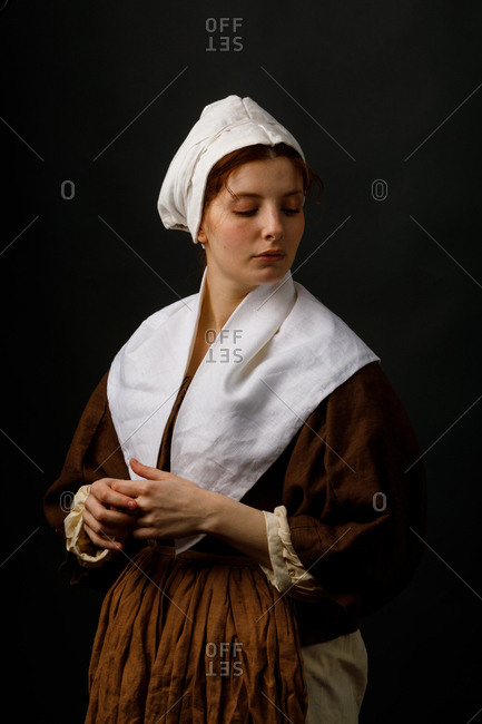 Pretty female in simple medieval clothing keeping eyes closed while standing on black background