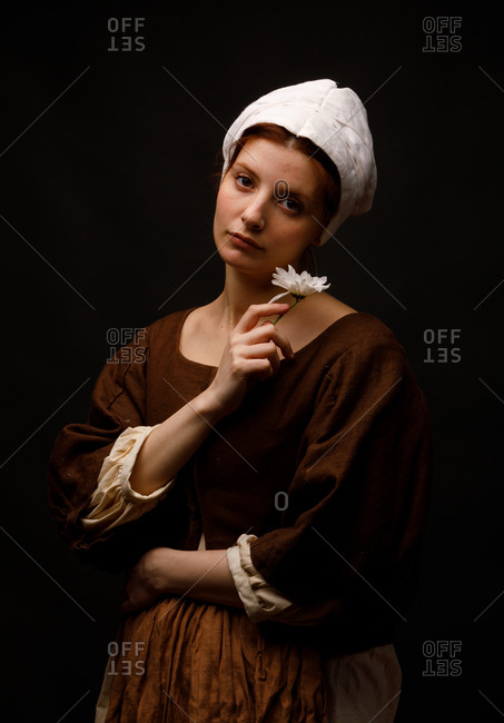 Attractive woman in medieval dress holding small white flower and looking at camera while standing on black background