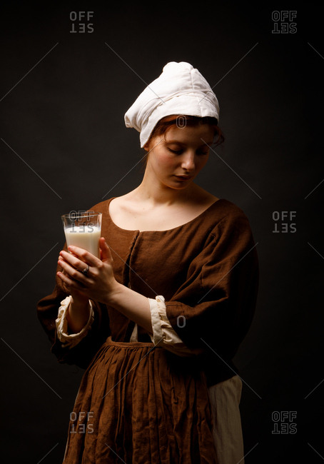 Pretty woman in simple medieval dress keeping eyes closed and holding glass of fresh milk while standing on black background