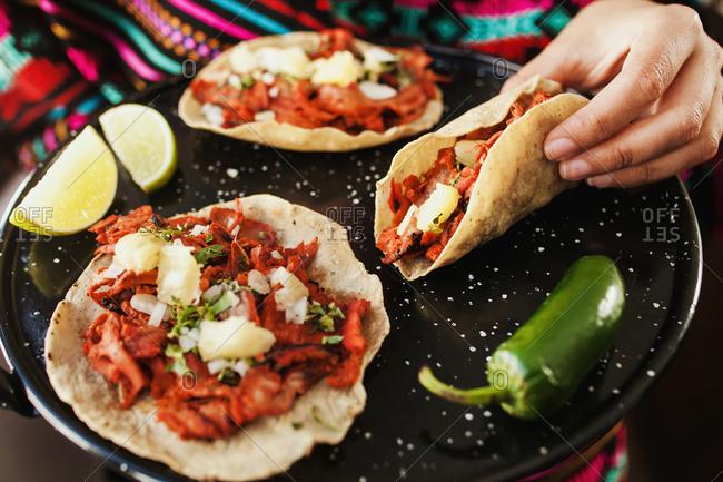 Crop hand holding taco al pastor