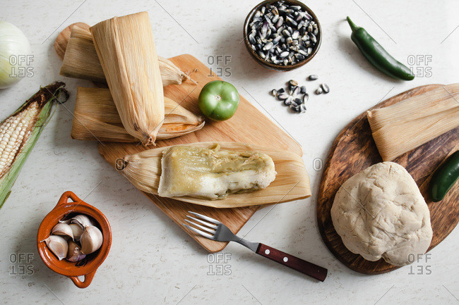 From above soft dough and corn husks lying near garlic and pepper for tamales on white tabletop