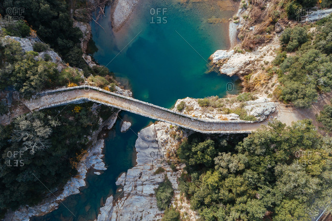 Breathtaking drone view of ancient bridge over calm blue river in wonderful countryside