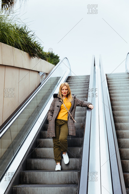 Blonde girl going down escalators in shopping center