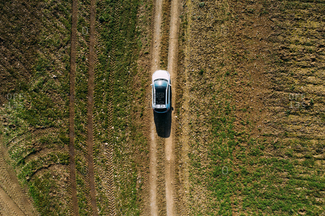 Aerial view of a car crossing a dirt road