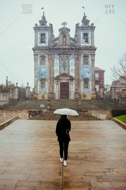 Back view of female with white umbrella walking on old pavement towards beautiful church building on rainy day in Porto, Portugal