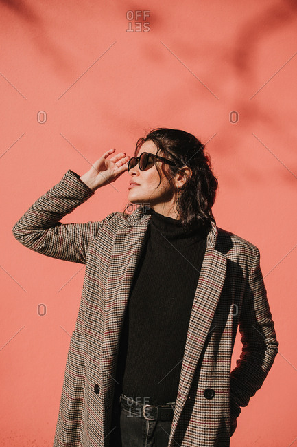 Beautiful trendy young woman in coat holding sunglasses and looking away on pink background