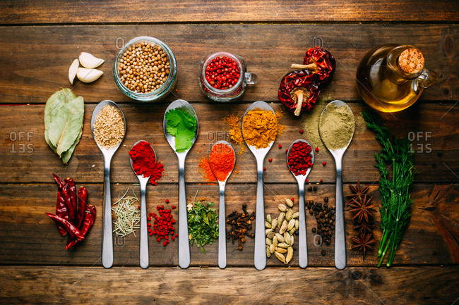 Bunch of assorted spices placed in order on lumber tabletop near bottle of oil