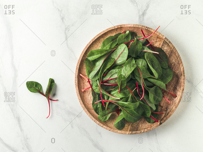 Fresh salad of green chard leaves or mangold on white marble background. Flat lay or top view fresh baby beet leaves on wooden plate. Copy space for text.