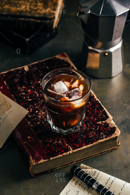 Cold espresso coffee glass in dark grunge mood with antique book