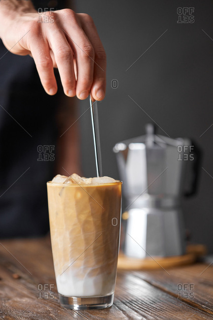 On a wooden table a transparent glass with ice a coffee drink and a geyzero coffee maker. A man's hand holds a spoon in a glass on a black background with copy space. Cooking frappe.