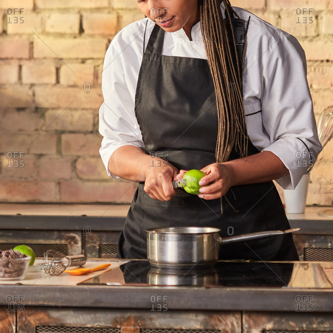 Woman baker cuts lime peel for cooking homemade desserts, green mint on the kitchen table on a brick wall background. Fresh natural ingredients for desserts. Step by step dessert making process.