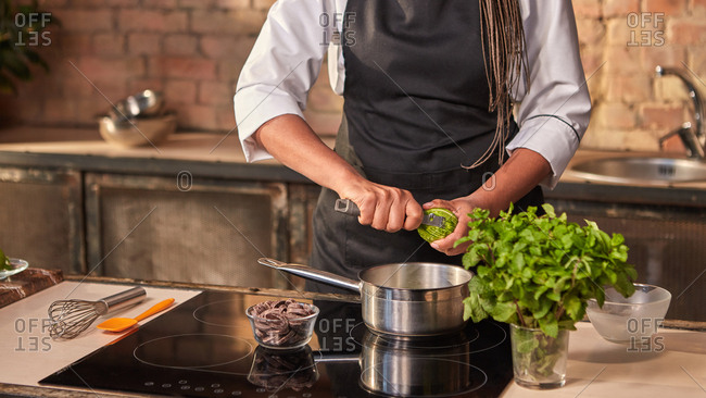 Professional confectioner cuts fresh lime peel into pan for cooking dessert on a hob at the kitchen table. Concept homemade sweets. Step by step dessert making process.