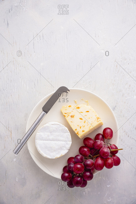 plate of cheeses and grapes