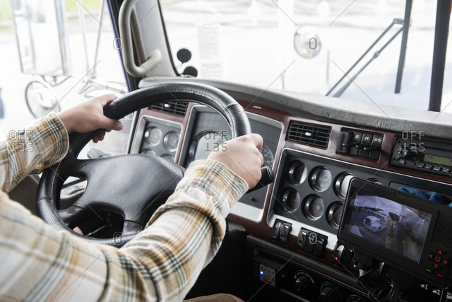 Hands of truck driver operating semi-truck