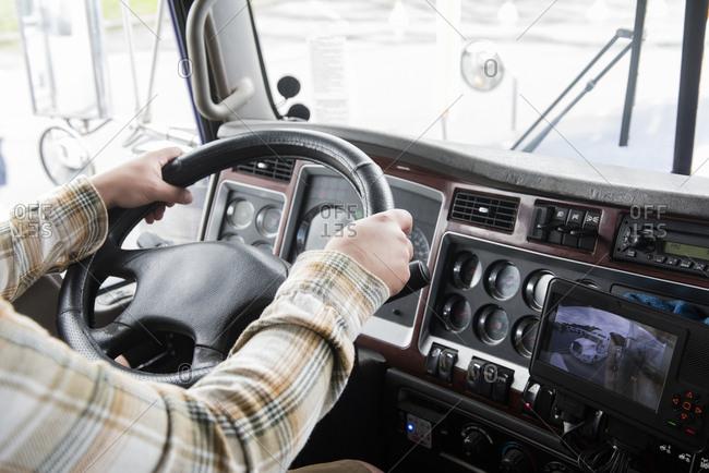 Hands of truck driver operating semi-truck