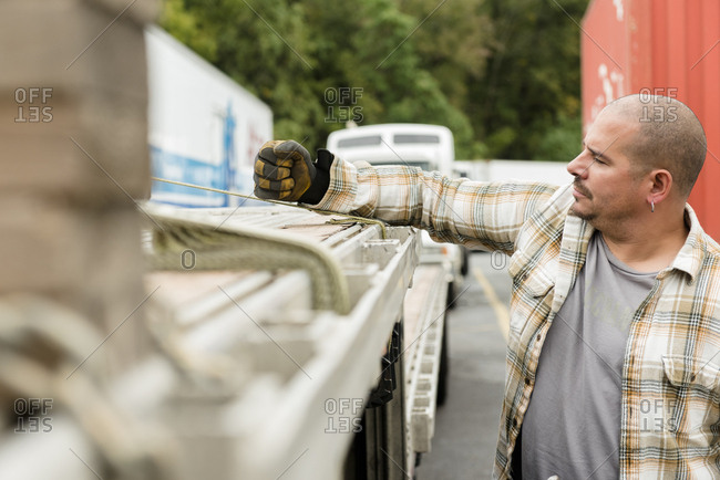 Truck driver fastening wood planks to his semi-truck