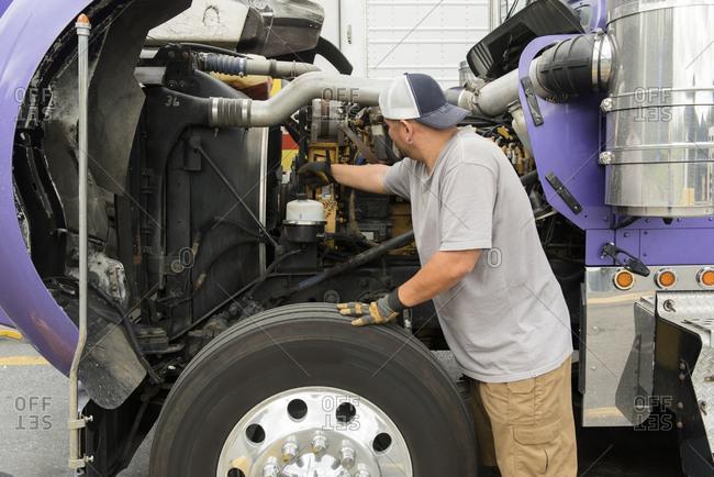 Truck driver checking semi-truck engine