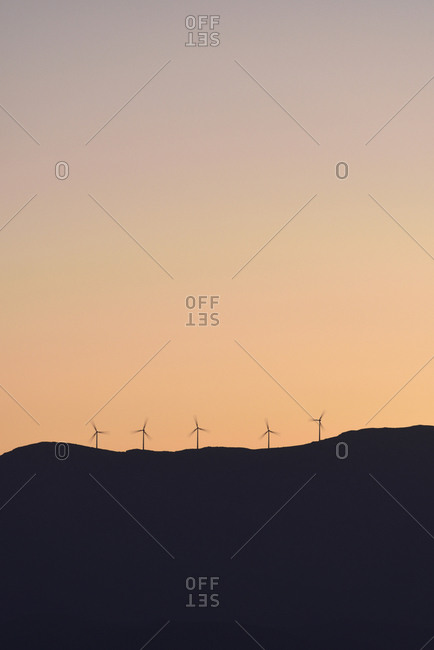 Silhouette of wind turbines on hill at sunset