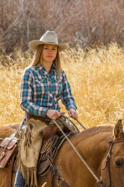 Teenage girl in cowboy hat horseback riding