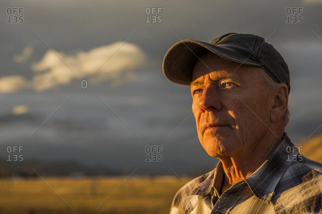 Senior man in baseball cap at sunset