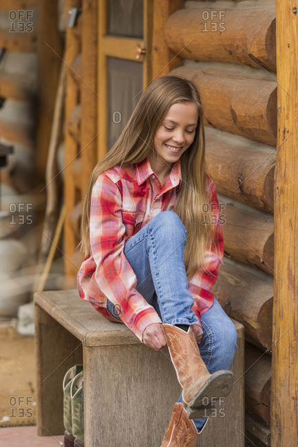 Girl putting on cowboy boots
