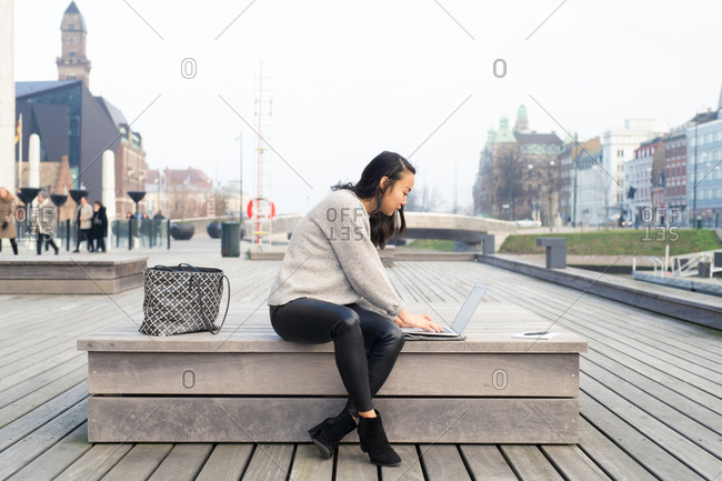 College student sitting on park bench working on laptop