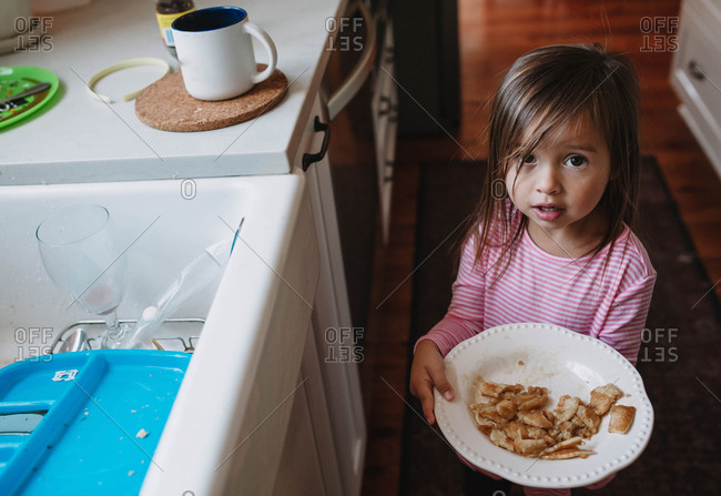 Toddler carrying her plate of food