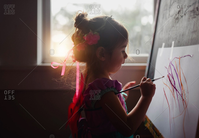 Toddler painting while wearing fairy princess costume