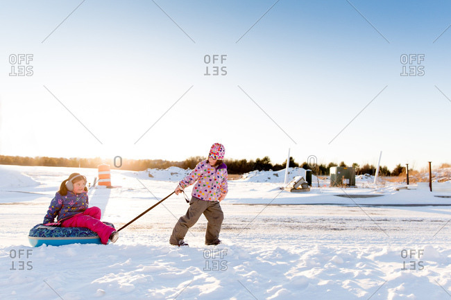 Girl pulling sister on a snow tube