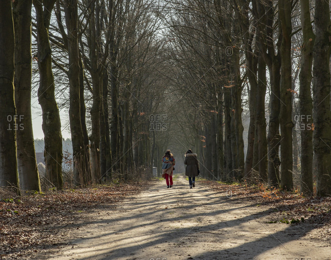 Two woman walking on dirt path in forest