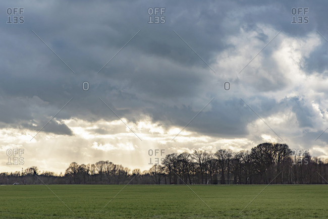 Sun shining through clouds over rural landscape