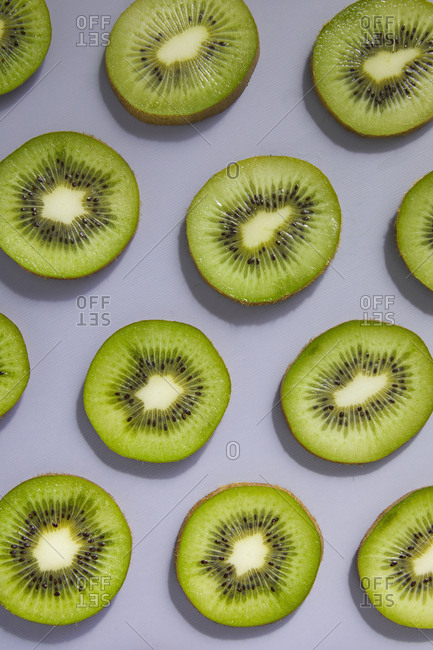 Kiwi fruit slices on gray background