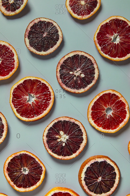 Blood orange fruit slices on a blue background