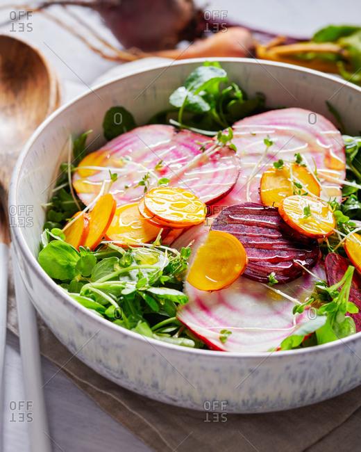 Vegan beetroot salad with mixed raw beets watercress and arugula with lemon dressing