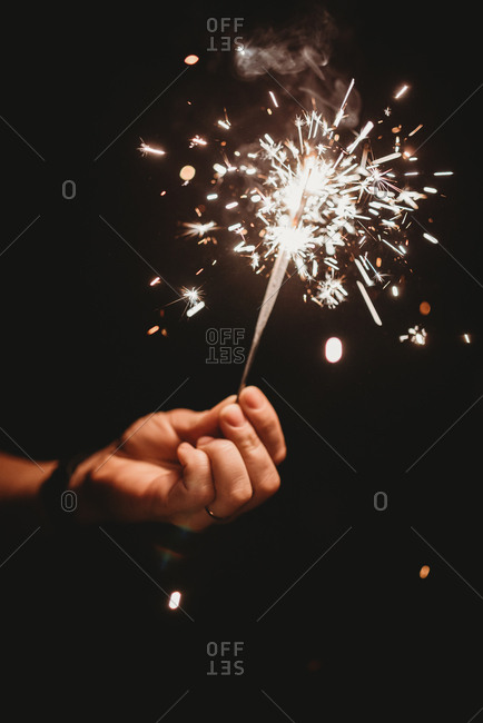 Hand holding a sparkler at nighttime