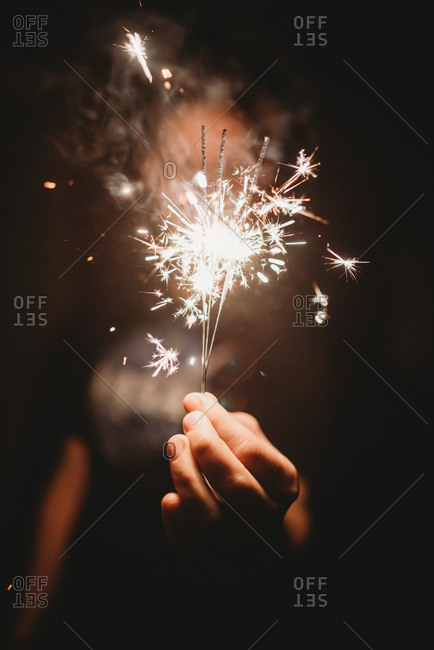 Hand holding several sparklers at nighttime