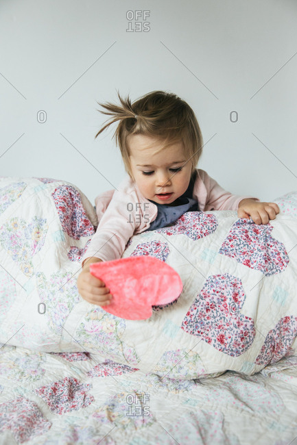 Toddler girl reaching for a paper heart