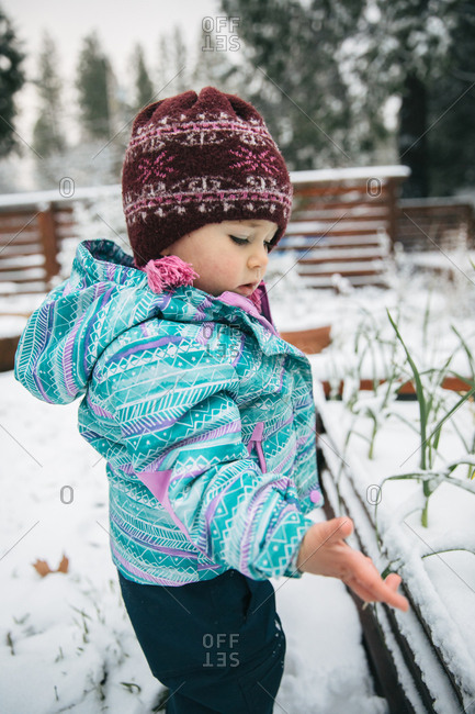 Little girl touching snow
